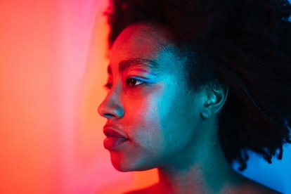 Portrait of a young edgy woman under neon lights; studio shot, isolated.