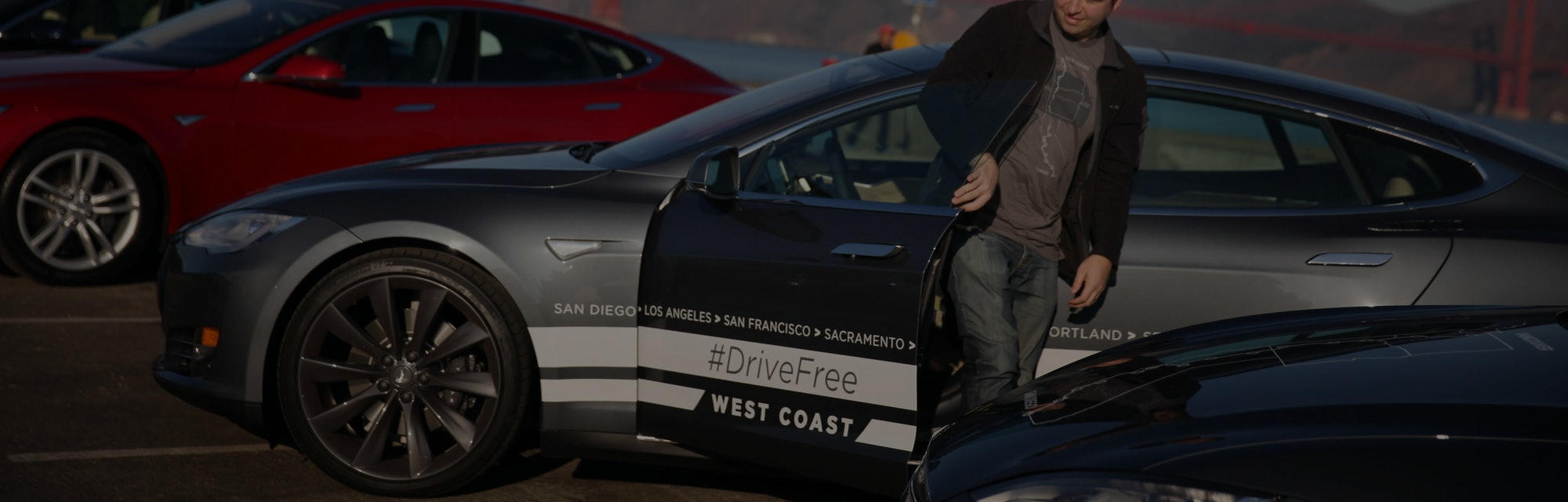 Daniel Myggen, Tesla sales operations, gets out of a Tesla Model S after parking it during a stop in...