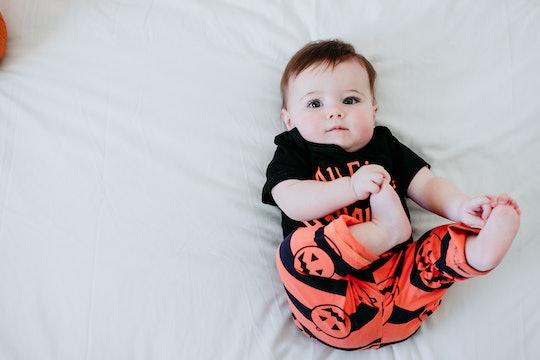 baby wearing halloween jack o' lantern pants