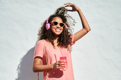Young woman with headphones and lemonade in front of white wall in sunlight, having the best week of...