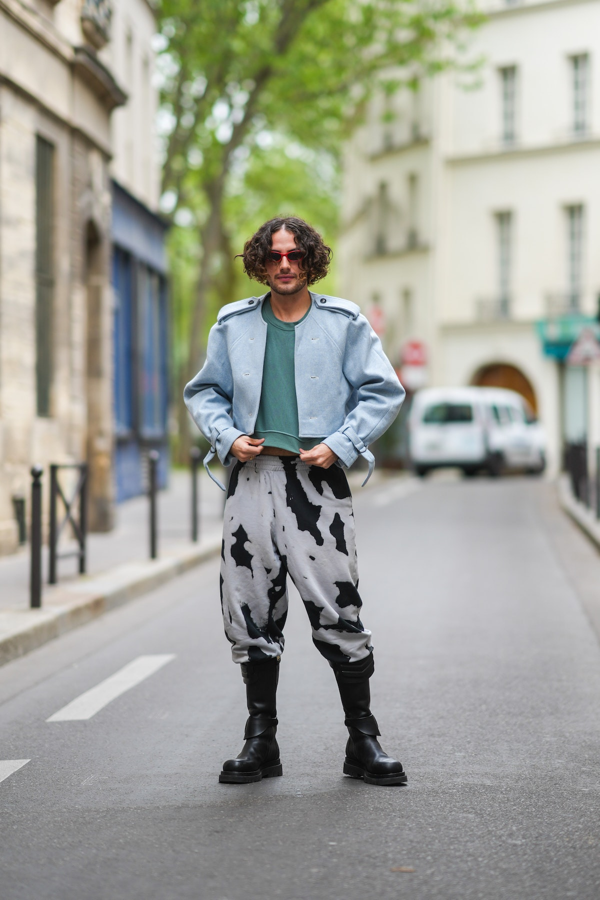 Alejandro Acero demonstrates how to wear combat boots with statement tie-dye sweatpants, a green shirt and a blue jacket