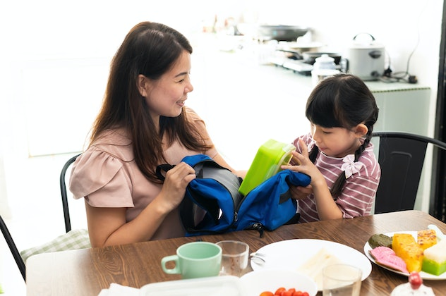 Young Asian mother preparing healthy lunch box for her daughter in the kitchen.