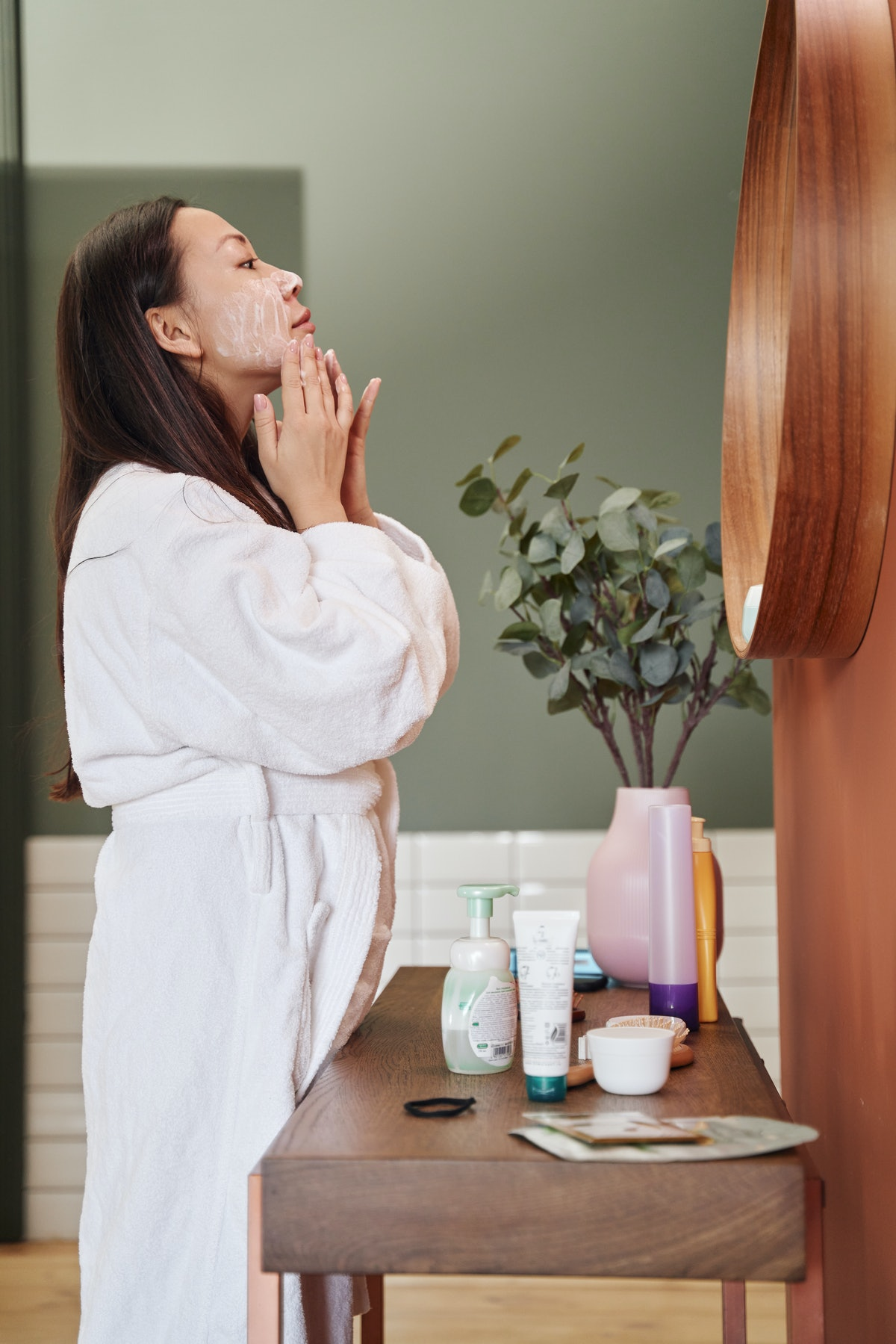 A woman standing in front of her bathroom mirror applying a face moisturizer