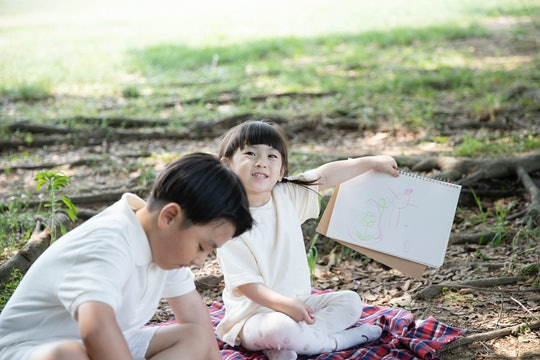 kids coloring outside, a girl and a boy