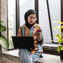 A woman wearing hijab searches for a dating app match on Instagram