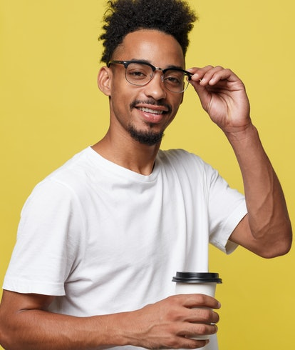 Stylish young afro american man holding cup of take away coffee isolated over yellow background.