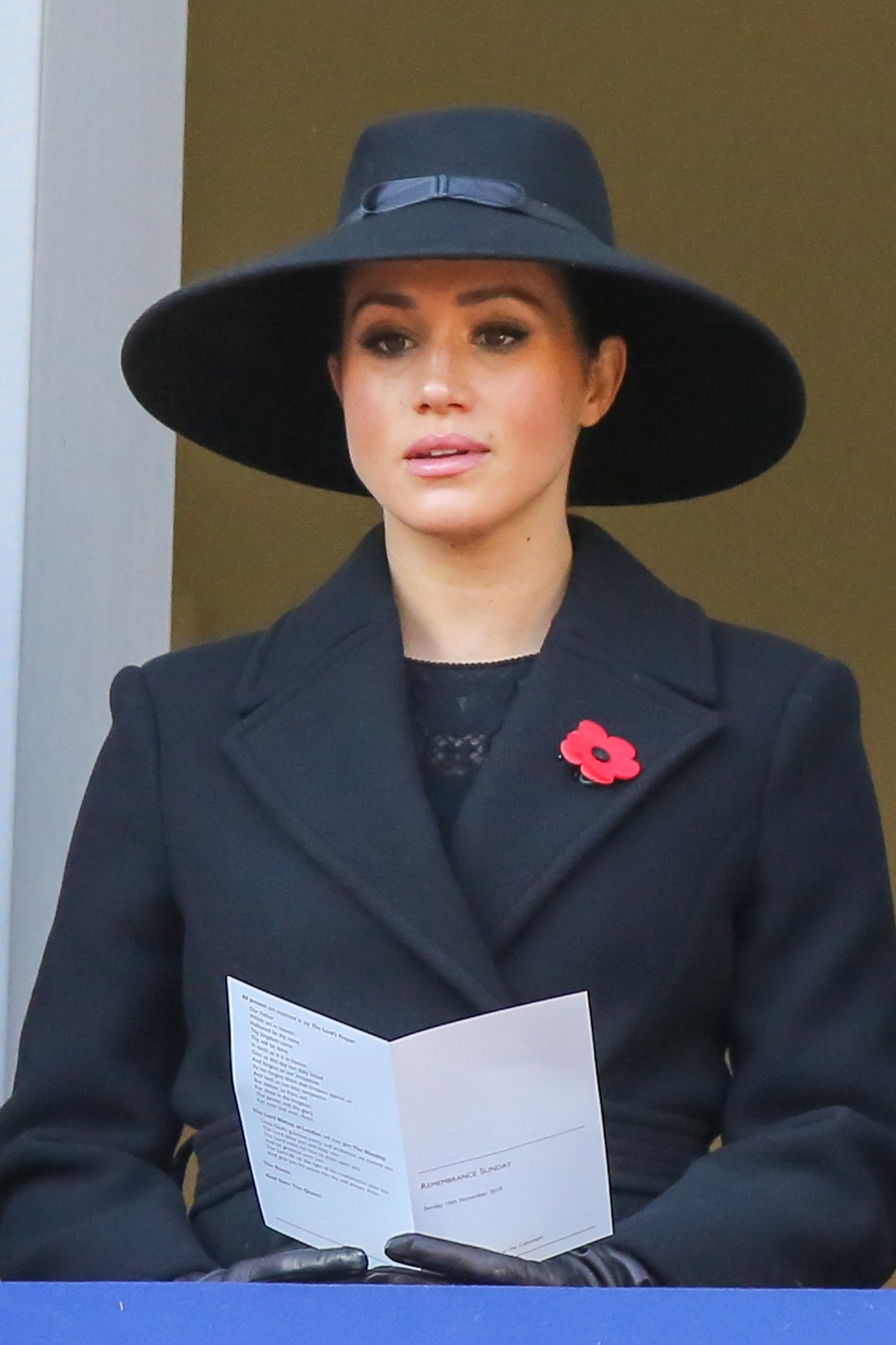 Here, Markle is shown sitting while wearing an all black ensemble consisting of a large hat, coat, a...