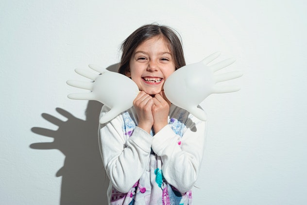 Little girl playing with surgeon gloves inflated like a balloon.