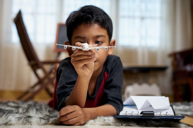 Boy making paper airplanes.