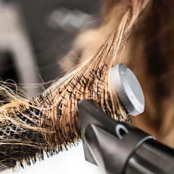 Young woman at a hair salon with hairdresser ,hair drying