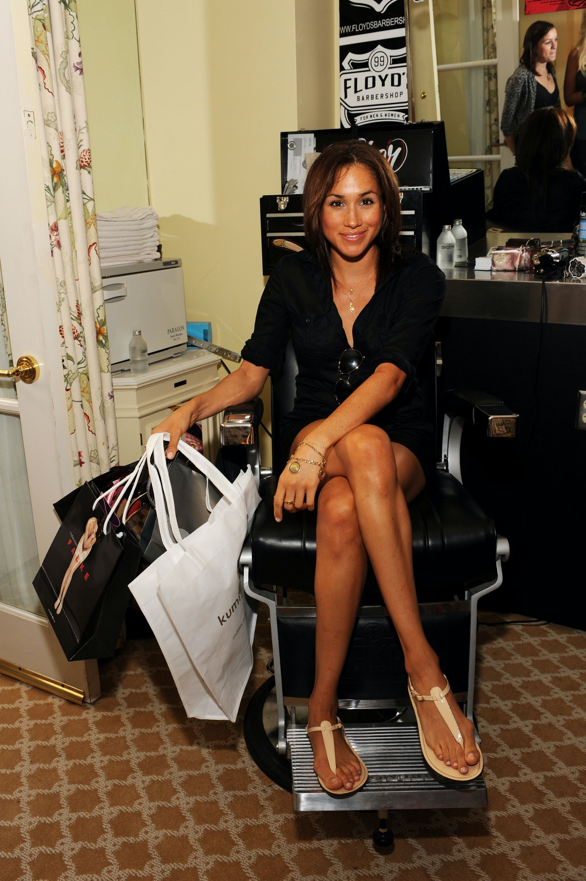 Shown here in a casual black shirt and sandals while sitting in a salon chair at an event, Markle at...