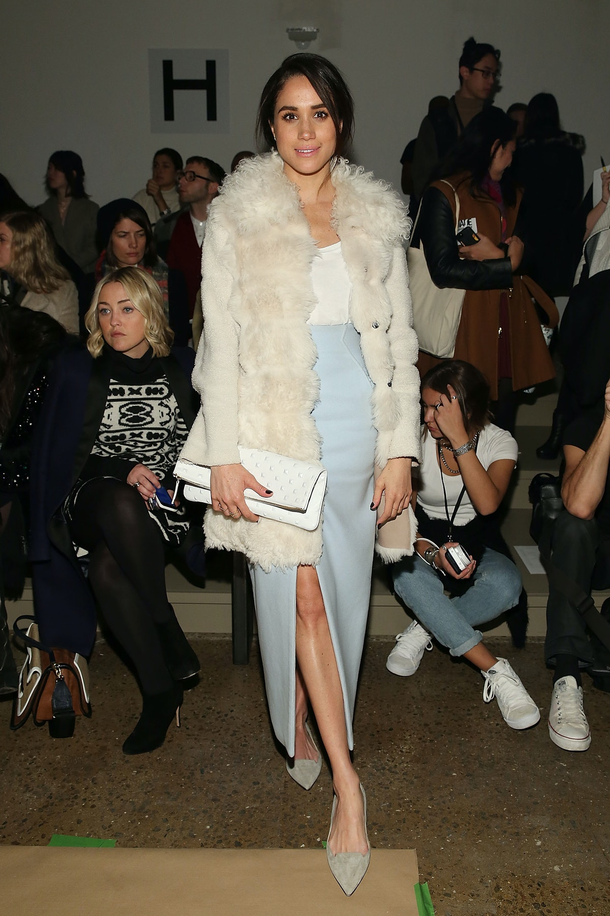 Markle, shown here in a baby blue skirt, a white top, and a cream fur coat, began rocking bolder loo...