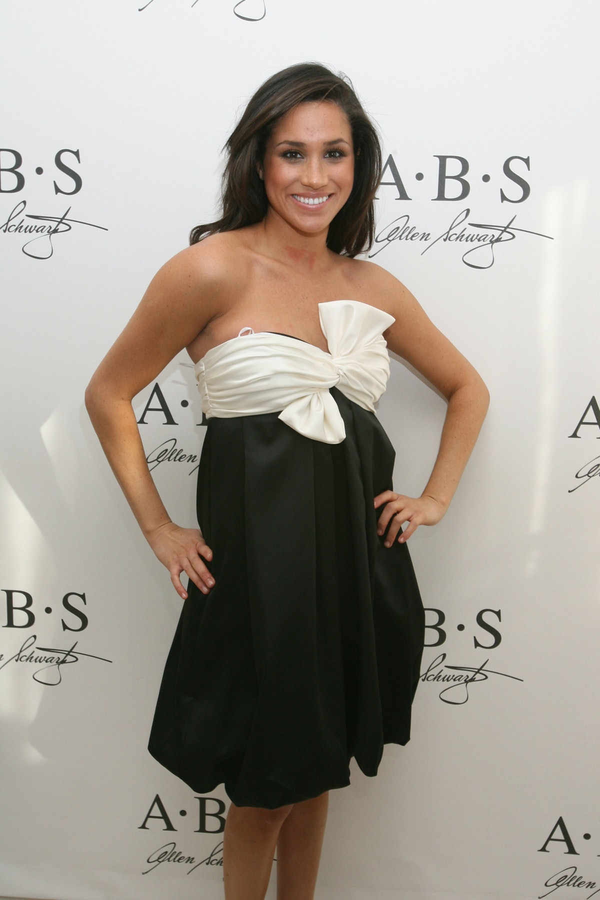Markle, pictured here smiling at a premiere in a black and white tube top dress with a bow on it, wa...