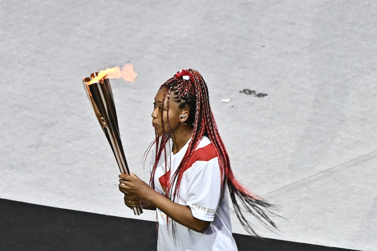 Japan's tennis player Naomi Osaka carries the Olympic torch in the Olympic Stadium during the openin...