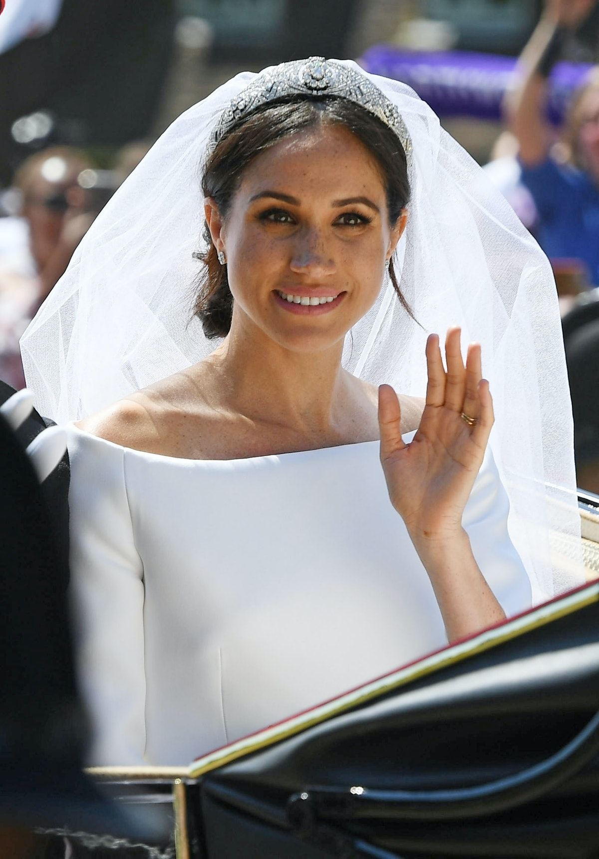 Meghan, the Duchess of Sussex, is shown here on her wedding day in a white off the shoulder dress, v...