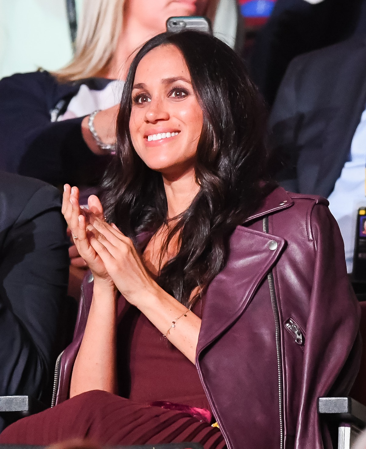 Markle, shown here in a burgundy dress and matching motorcycle jacket, applauded at the Invictus Gam...
