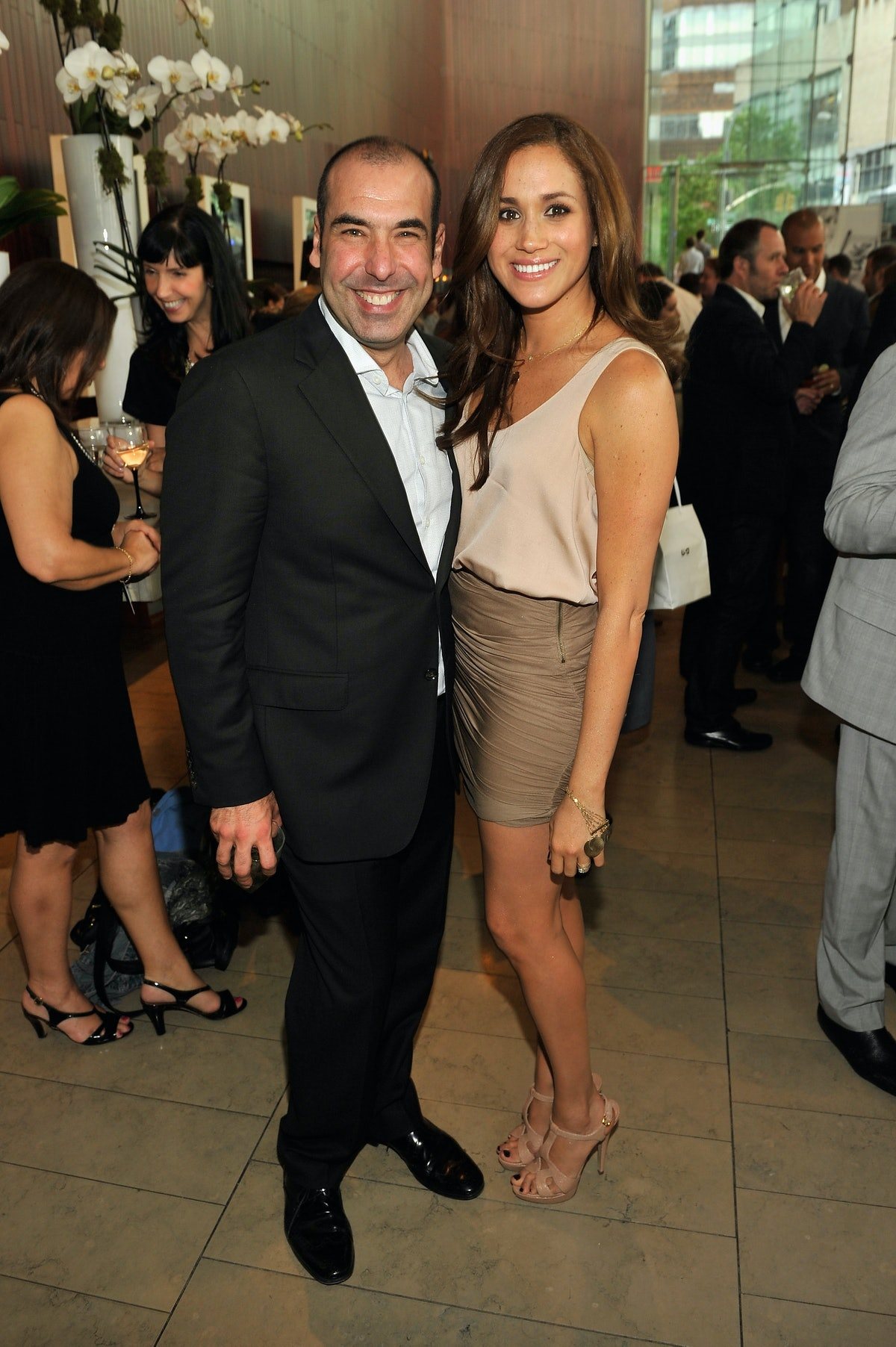 Markle, shown here in a taupe blouse and tan skirt with her suits co-star Rick Hoffman, gets close w...