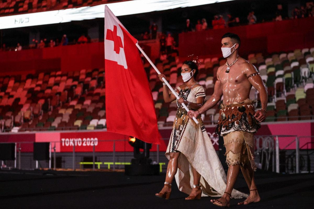 TOPSHOT - Tonga's flag bearers Malia Paseka (L) and Pita Taufatofua lead the delegation during the T...