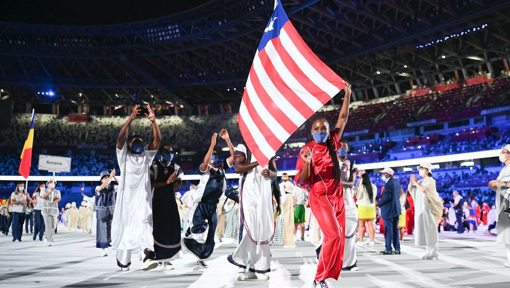 TOKYO, JAPAN - JULY 23: Flag bearers Ebony Morrison and Joseph Fahnbulleh of Team Liberia walk their...