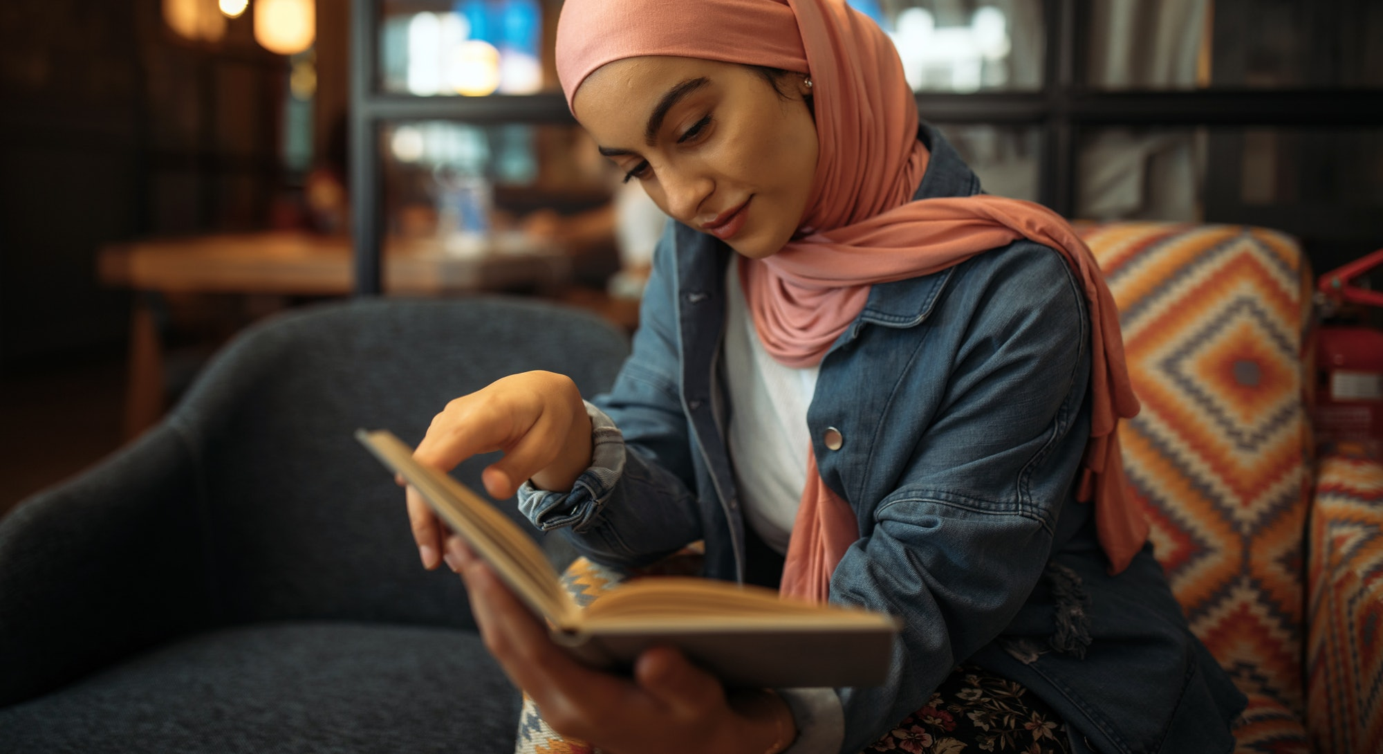 Young muslim woman in hijab reading book at cafe