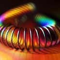 Titanium-coated metal spring on holographic foil with rainbow light effects. Low key lighting.