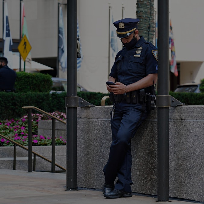 NEW YORK, NEW YORK - AUGUST 01:  An NYPD officer wearing a protective mask looks at his phone at Rockefeller Center as the city continues Phase 4 of re-opening following restrictions imposed to slow the spread of coronavirus on August 1, 2020 in New York City. The fourth phase allows outdoor arts and entertainment, sporting events without fans and media production. (Photo by Cindy Ord/Getty Images)