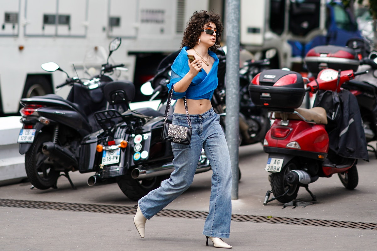 A woman with curly hair demonstrates how to wear low-rise jeans, which are making a comeback