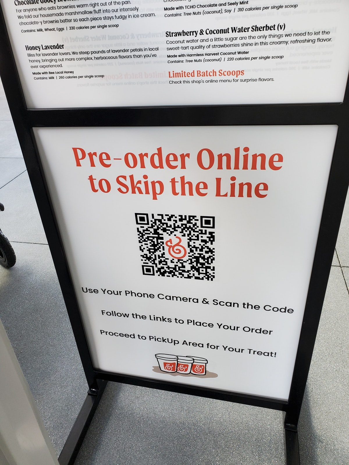 """Close-up of a QR coded """"Pre-order Online to Skip the Line"""" and menu sign outside a Salt and Straw ic..."""