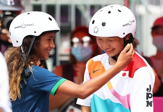 TOKYO, JAPAN - JULY 26:  Rayssa Leal of Team Brazil puts her hand up to the face of Momiji Nishiya o...