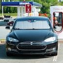 Enfield, Canada - June 7, 2021 - A Tesla Model S sedan at a Supercharger charging terminal at a gas ...