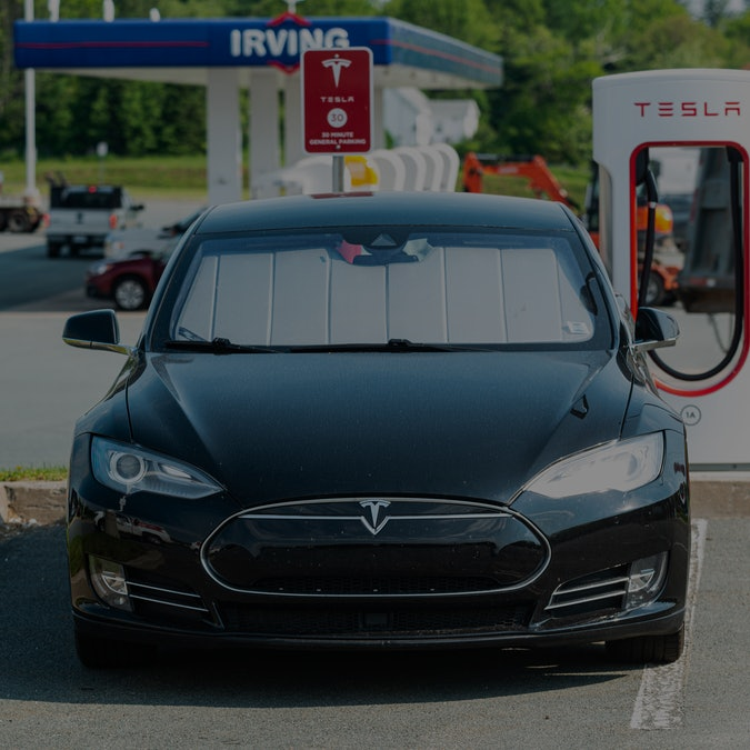Enfield, Canada - June 7, 2021 - A Tesla Model S sedan at a Supercharger charging terminal at a gas station.