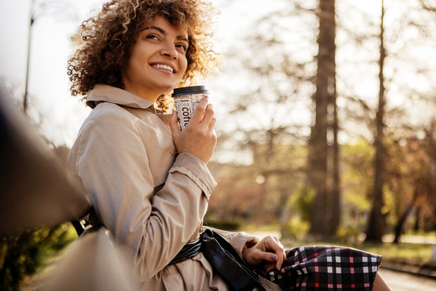 Beautiful young woman smiling with eyes closed drinking a takeaway cup of coffee outside