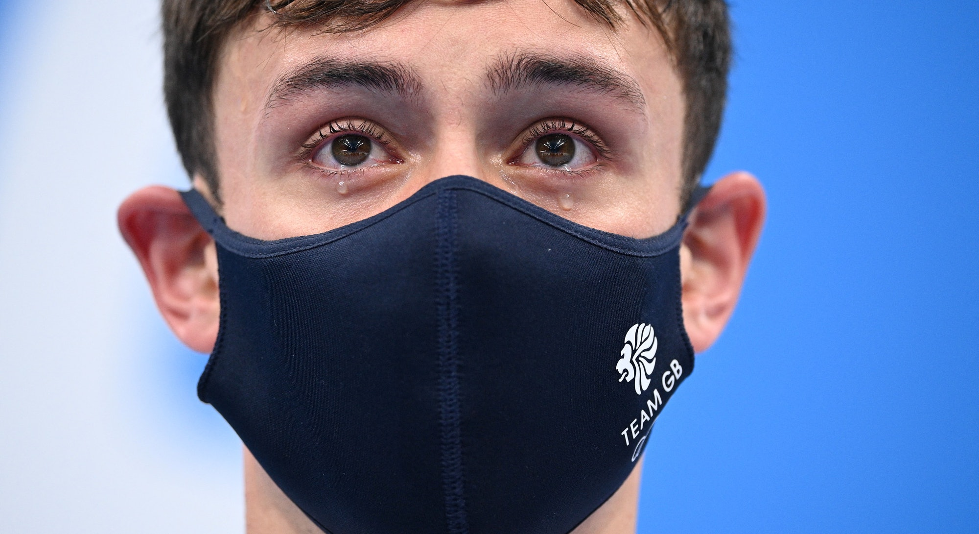 Tears well in the eyes of gold medallists Britain's Thomas Daley and Britain's Matty Lee (unseen) as...