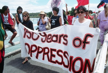 """Protesters hold a banner reading """"150 years of OPPRESSION"""" during Queen Elizabeth's visit to New Zea..."""