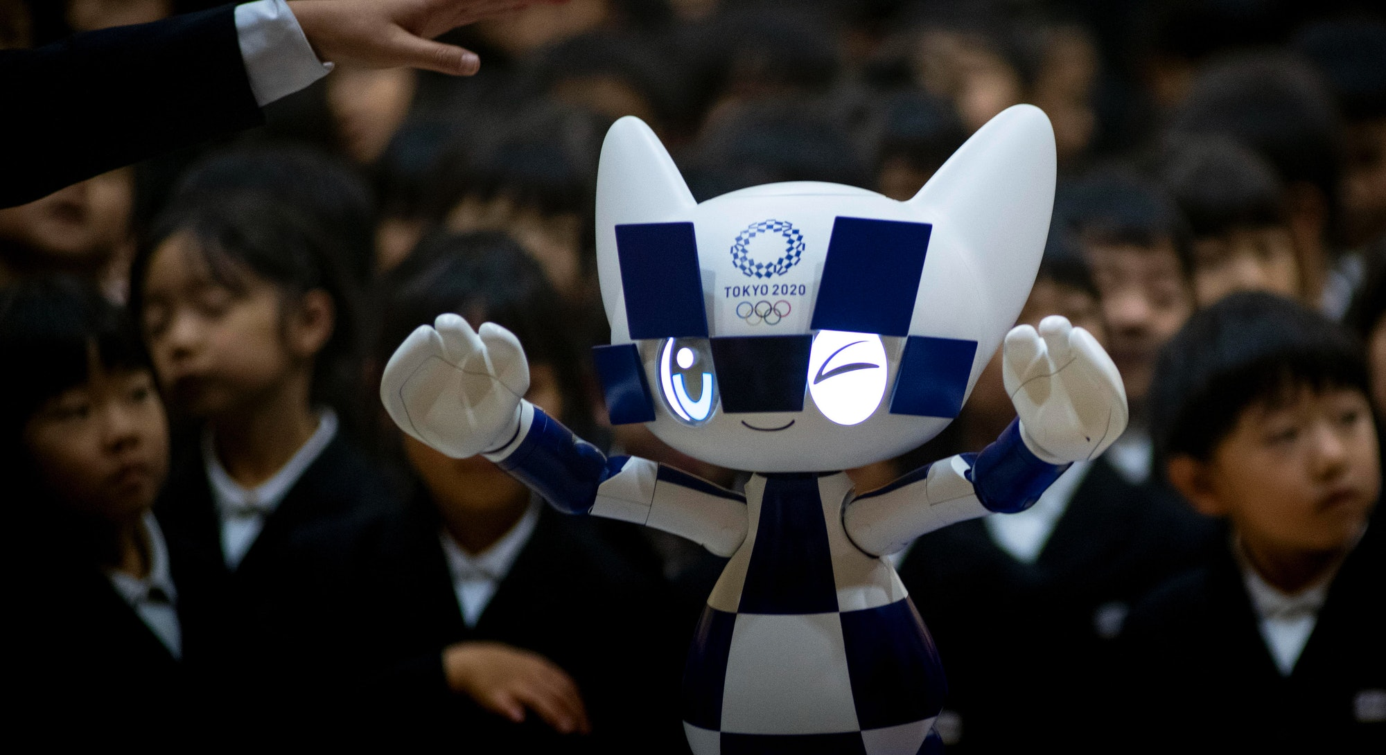 Schoolchildren pose for a picture with Tokyo 2020 Olympic Games' robot-type mascot Miraitowa during ...