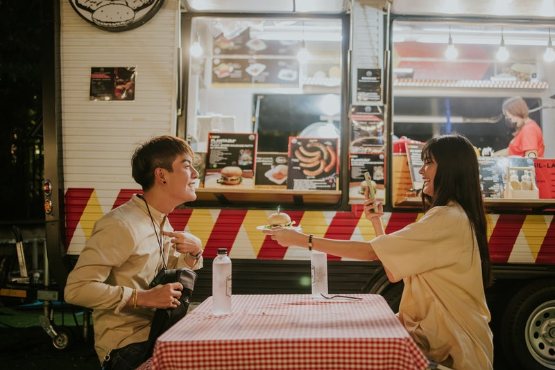 Teenage boy introduce himself with a hamburger for live streaming while dining with girlfriend to ma...