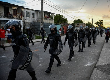 TOPSHOT - Riot police walk the streets after a demonstration against the government of President Mig...