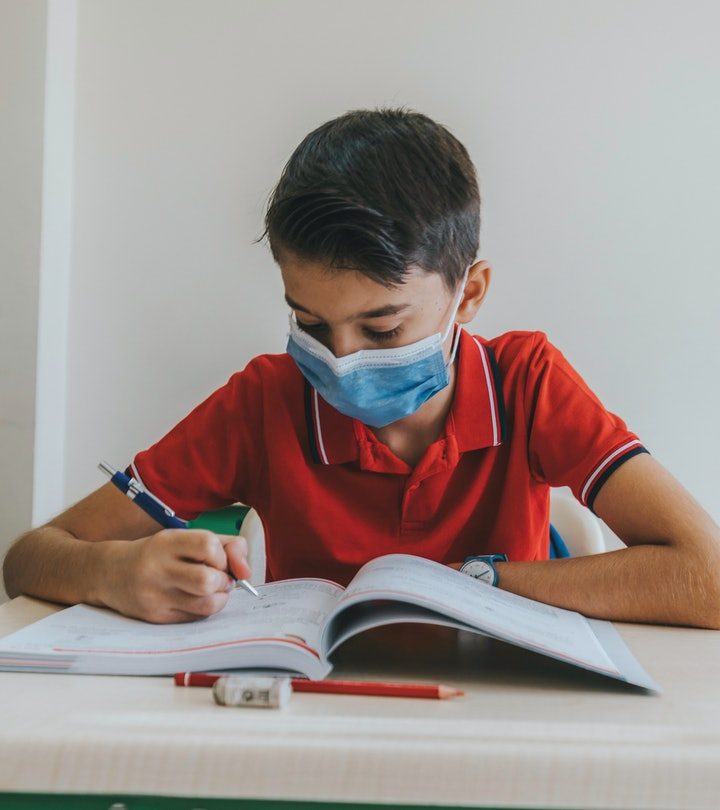 boy with face mask working at school desk