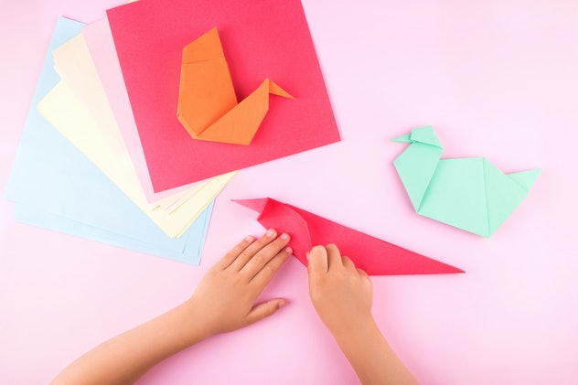 Little girl making origami from colorful paper at the table at home.