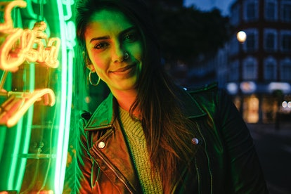 Young woman in green neon lights, preparing for new moon in Leo.