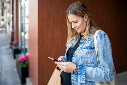 Pregnant woman standing and using mobile phone