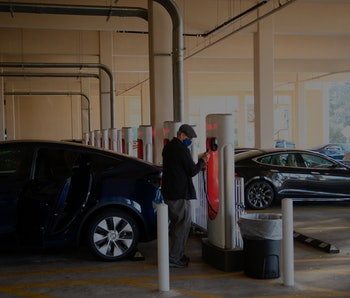 Tesla Inc. electric vehicles charge at the company's supercharger station inside a parking garage on...
