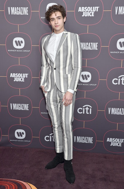 Joshua Bassett, shown here at a premiere while wearing a grey striped suit, is in his feels.