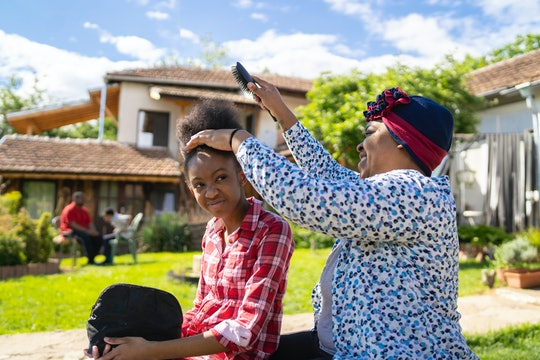 Afro-American mom is brushing her daughters' hair while they are sitting outside in the sunshine of ...