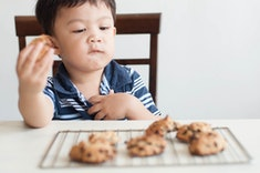 a little boy eating chocolate chip cookies