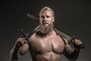 Weapon wielding viking warrior Odin god in studio shot