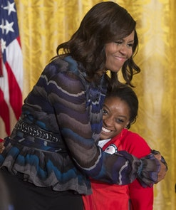 US First Lady Michelle Obama hugs US Olympic gymnast Simone Biles during a ceremony honoring the 201...