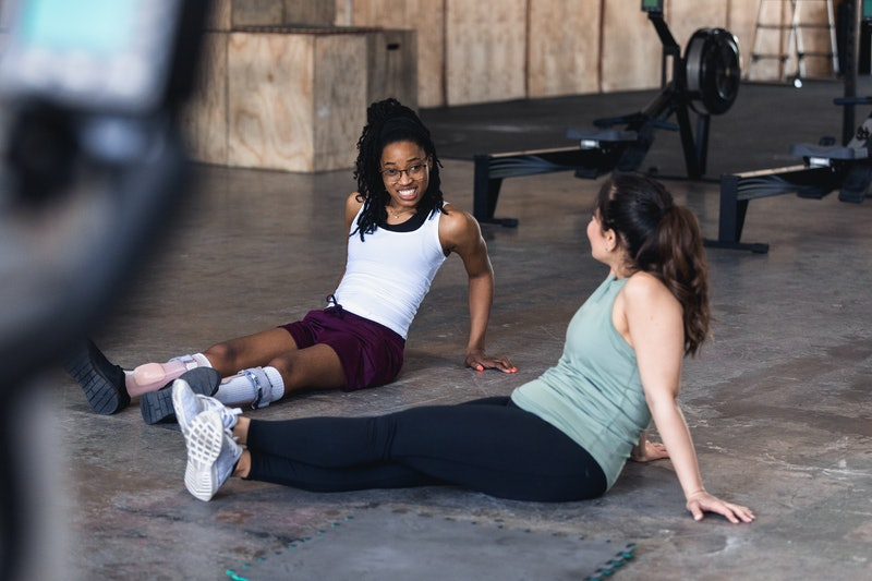 The mid adult female trainer sits on the gym floor with her young adult female client to relax after...