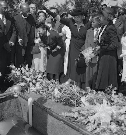 (Original Caption) Friends restrain grief-stricken Mrs. Mamie Bradley (left) as her son's body is lo...