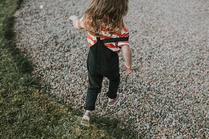 little girl skipping along a gravel road